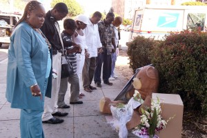 Unidentified mourners observe a moment of prayer at the spot where Oakland Post editor Chauncey Bailey was gunned down Aug. 2, 2007, in Oakland (D. Ross Cameron/The Oakland Tribune)