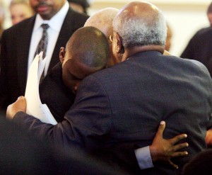 Oakland Post publisher Paul Cobb, back to camera, embraces Chauncey Bailey III, left, and grandfather Chauncey Bailey Sr. (partially hidden) during the funeral for Oakland Post editor Chauncey Bailey Jr. Aug. 8, 2007 in Oakland (D. Ross Cameron/The Oakland Tribune)