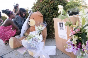 Felecia Brown, second from left, and daughter Unyque sign a note of condolence at a memorial on the spot where Oakland Post editor Chauncey Bailey was gunned down Aug. 2, 2007, in Oakland.  Brown said she was a student of Bailey's when he was working at KDIA radio. (D. Ross Cameron/The Oakland Tribune)