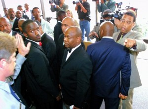 Followers of Yusuf Bey block the press from elevators as Bey leaves the courthouse Sept. 26, 2002. Chauncey Bailey is at right in gray suit. (Nick Lammers/Oakland Tribune)