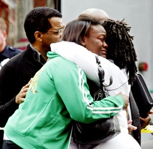 Unidentified colleagues of Oakland Post editor Chauncey Bailey console each other at the scene where Bailey was slain Aug. 2, 2007 (D. Ross Cameron/The Oakland Tribune)