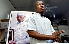 Antar Bey stands in front of a portrait of his father, Your Black Muslim Bakery patriarch Yusuf Bey, before his death in 2005. (Oakland Tribune)