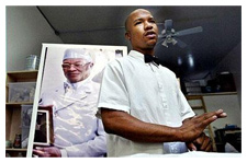 Antar Bey poses in front of a portrait of his father, Your Black Muslim Bakery patriarch Yusuf Bey, before his death in 2005. (Oakland Tribune)