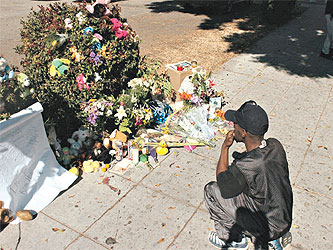 Detrick Moore of Oakland looks at a memorial for Chauncey Bailey before a community mobilization event in Oakland in August 2007. (Sean Connelley, Oakland Tribune)