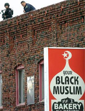 A sharpshooter keeps watch atop Your Black Muslim Bakery in Oakland, Calif., following a pre-dawn raid on Aug. 3, 2007. Police said they raided four locations this morning as part of a yearlong investigation into charges against people at the bakery including murder, robbery and kidnapping. (Noah Berger, Associated Press)