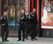 Swat team members and Oakland police officers stand in front of Your Black Muslim Bakery on San Pablo Avenue after an early morning raid in Oakland, Calif., on Aug. 3, 2007. The building is being transformed into a new business. (Laura A. Oda, Oakland Tribune).