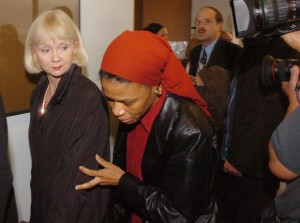 Daulet Bey, red scarf, leaves Oakland courtroom in 2005 where her son, Yusuf Bey IV, was charged with hate crimes and felony vandalism. (Bob Larson/Contra Costa Times)