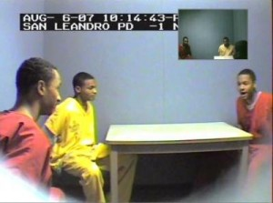 """In a secretly recorded police video from Aug. 6, suspects being held in a torture and kidnapping case, Joshua Bey (left) and Tamon Halfin watch as Your Black Muslim Bakery leader Yusuf Bey IV demonstrates the Aug. 2 killing of Chauncey Bailey. \""""Pow, pow, poof,\"""" Bey IV says, throwing back his head. (Oakland Police Video)"""